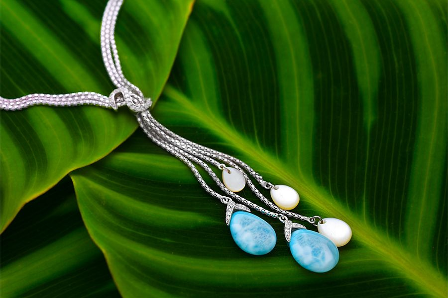 The Marahlago Enigma Larimar necklace is displayed on a green leaf.