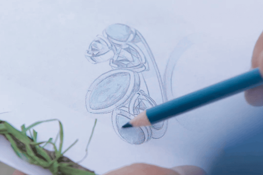 The Marahlago designer is hand drawing a jewelry piece in blue pencil.